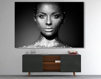 Fashion model woman in bright sparkles and lights posing in studio. Portrait of beautiful sexy woman. Art design glitter glowing make up. Black and white photography