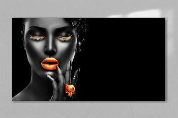 Fashion model with black skin, golden lips, eyelashes and jewellery - golden ring on hand. Isolated on black background. Beauty woman face, beautiful make-up. Gorgeous lady fashion art portrait.