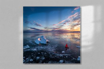 Greenland early Sunrise iceberg aerial view with red sail ship