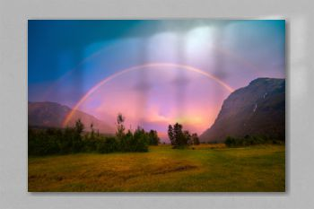 Beautiful rainbow over the mountains during sunset. Wilderness Norway