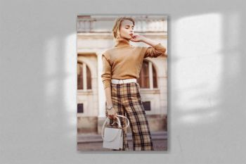 Outdoor fashion portrait of young beautiful fashionable girl wearing trendy beige cashmere turtleneck, high-waisted checkered trousers, belt, wrist watch, holding small white bag, posing in street