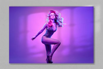 Gorgeous Disco Party girl with glowing hair, makeup. High Fashion. Young beautiful model woman in Colorful neon purple Light. Night Clubbing. Creative art style