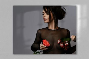 Portrait of young beautiful sexy brunette woman in black transparent clothing holding flowers on nipples places