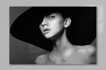 Portrait of a beautiful young girl in a hat, black and white photography in the studio