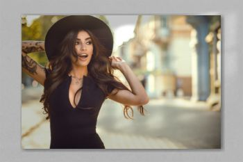 Portrait of gorgeous glam tattooed lady with long wavy hair and beautiful make up holding her trendy fedora hat for it not to be blown away by the wind. Her mouth open with surprise. Copy-space