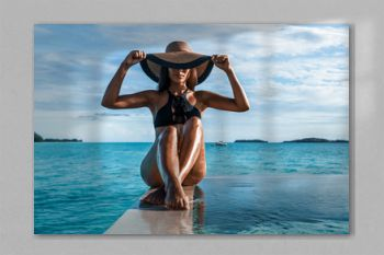 Elegant black swimsuit swimwear model woman with contrast brim sun hat on infinity pool luxury resort vacation. High end fashion for wellness spa , hair removal laser legs and body pedicure skincare.