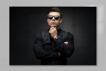Portrait of beautyful guy on dark background. High fashion model posing in studio. Attractive man in classic suit and sunglasses.