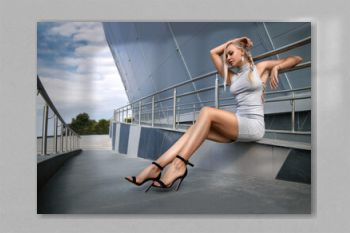 Beautiful blonde girl in a grey dress with perfect legs and shoes with high heels posing outdoor at the city square. Street fashion photo.