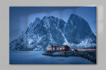 Red rorbu on sea coast and snow covered mountain at dusk. Lofoten islands, Norway. Moody winter landscape with traditional norwegian rorbuer, water, snowy rocks at night. Old fishermen's houses