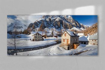 Panoramic view of the sunny snow-covered landscape of the village of Crampiolo, above the Alpe Devero in Piedmont, Italy.