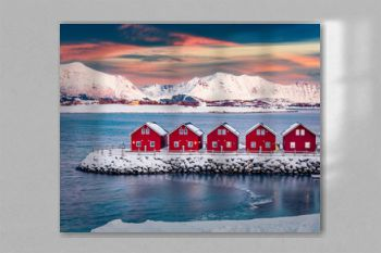 Traditional red wooden houses on the shore of Offersoystraumen fjord. Fantastic winter sunset on Vestvagoy island. Picturesque evening view of Lofoten Islands, Norway. Life over polar circle..