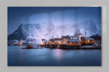 Rorbu on sea coast and snow covered mountain in fog at dusk. Lofoten islands, Norway. Moody winter landscape with traditional norwegian rorbuer, water, snowy rocks at night. Old fishermen's houses