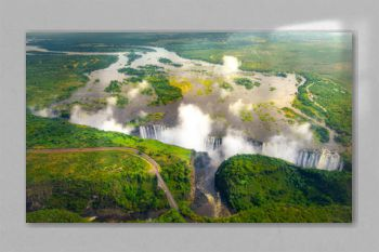 Victoria Falls in Zimbabwe and Zambia, Aerial helicopter photo, green forest around amazing majestic waterfalls of Africa. Livingston Bridge above the river