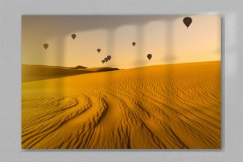 Sunset over the sand dunes in the desert with hot air balloons. Arid landscape of the Sahara desert